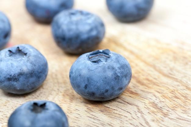 Blauwe rijpe sappige bessen bosbessen tot op een houten oppervlak. foto close-up. kleine scherptediepte. gefotografeerd van boven naar beneden.