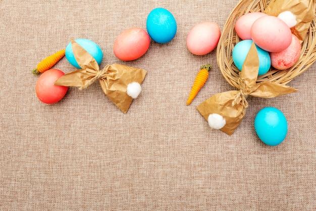 Blauwe, rode en roze eieren voor pasen met papieren konijntjes