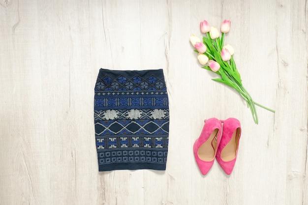 Blauwe rok met ornament, roze schoentjes en boeket tulpen. modieus concept