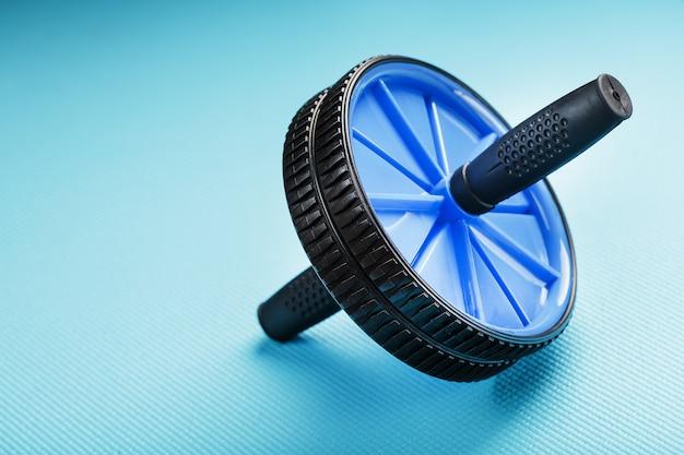 Blauwe roller voor buikspieren op een blauwe fitnessmat