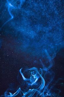 Blauwe rook en nevel van water op een zwarte achtergrond