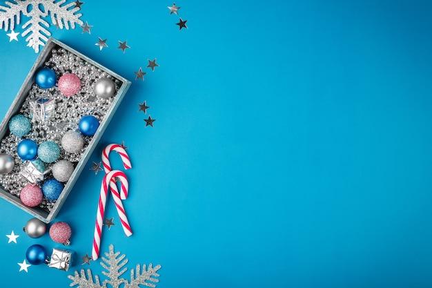 Blauwe, roze en zilveren kerstballen, zilveren kerstparels in een houten doos en zuurstokken op blauw. plat leggen. feestelijke rand voor wenskaart