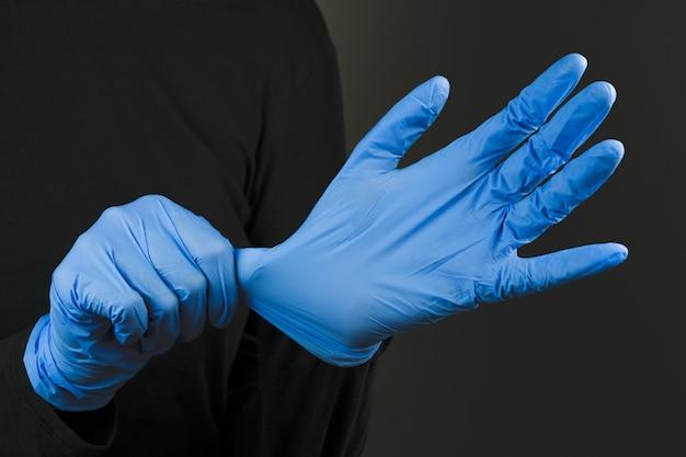 Blauwe rubberen handschoenen aantrekken. beschermende handuitrusting dragen tegen de infectie of virusverspreiding. covid-19, laboratorium of wetenschappelijk laboratoriumconcept