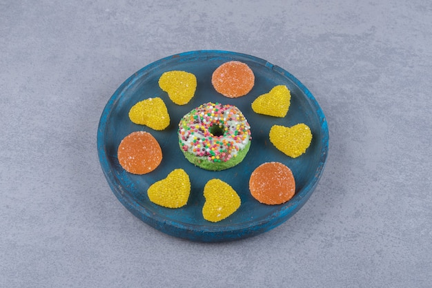 Blauwe schaal met een kleine donut en diverse marmelades op een marmeren ondergrond '