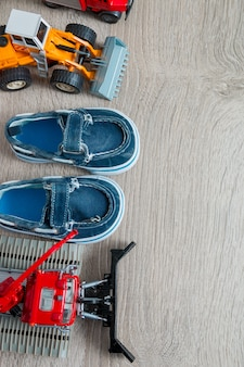 Blauwe schoenen voor kleine jongen in de buurt van speelgoedauto's
