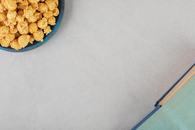 Blauwe schotel gevuld met caramal gecoate popcorn naast een open boek op marmeren achtergrond.