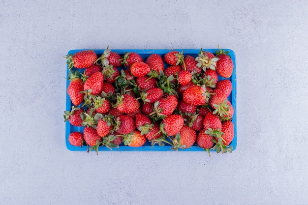 Blauwe schotel met een gedeelte van aardbeien op marmeren achtergrond. hoge kwaliteit foto