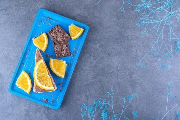 Blauwe schotel naast decoratieve takken, met een taartpunt, chocoladeborden en sinaasappelschijfjes op een marmeren oppervlak
