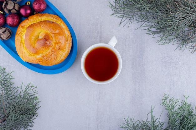 Blauwe schotel van zoet broodje en kerstversiering met een kopje thee op witte achtergrond.