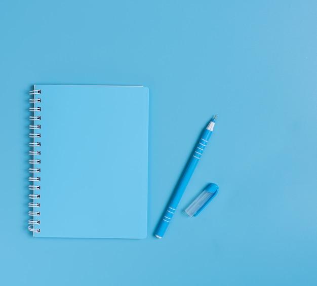 Blauwe set van notebook en pen ingesteld op blauw bureau, bovenaanzicht