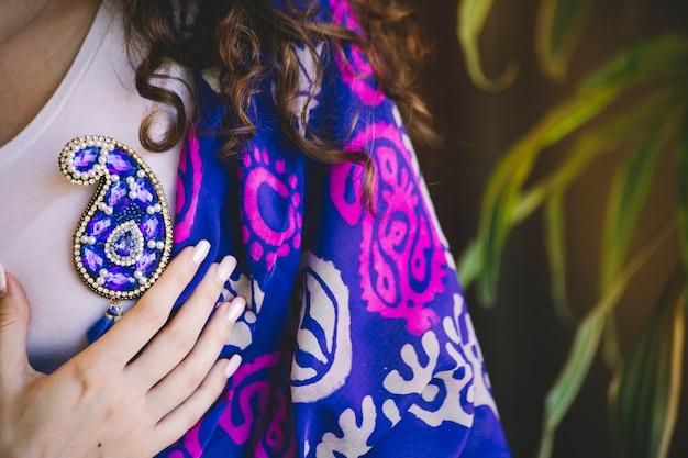 Blauwe sieradenspeld in butavorm en zijden sjaal