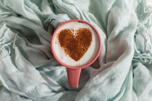 Blauwe sjaal, koffie met een hartpatroon op tafel, een goede morgen is de beste startdag. herfst stemming achtergrond, copyspace.