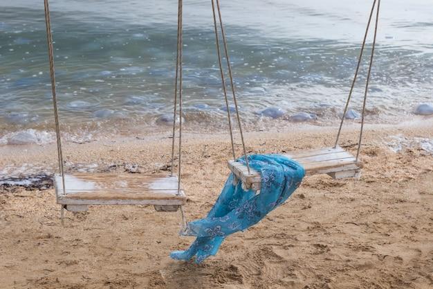Blauwe sjaal op een schommel over zee. algen op zand. kwallen in water.