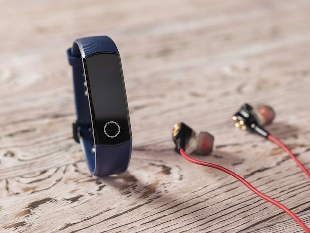Blauwe slimme armband en rode oortelefoons op houten tafel. accessoires om sporten te besturen. sportieve stijl.