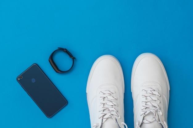Blauwe slimme armband, mobiele blauwe en witte sneakers met een blauwe achtergrond. sportieve stijl. plat leggen. het uitzicht vanaf de top.