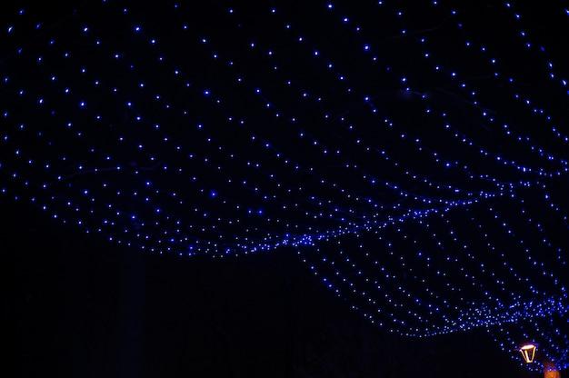 Blauwe slinger in het decor van kerstmis van het park van de winter