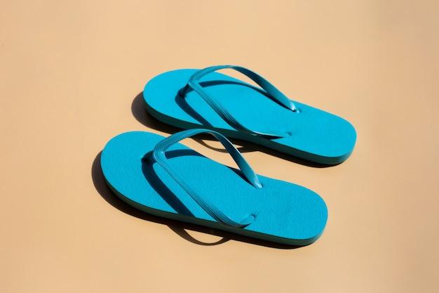 Blauwe slippers op bruine achtergrond.