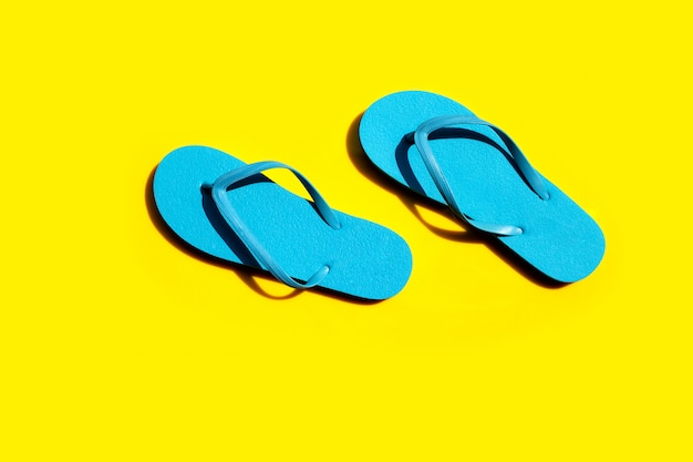 Blauwe slippers op gele achtergrond.