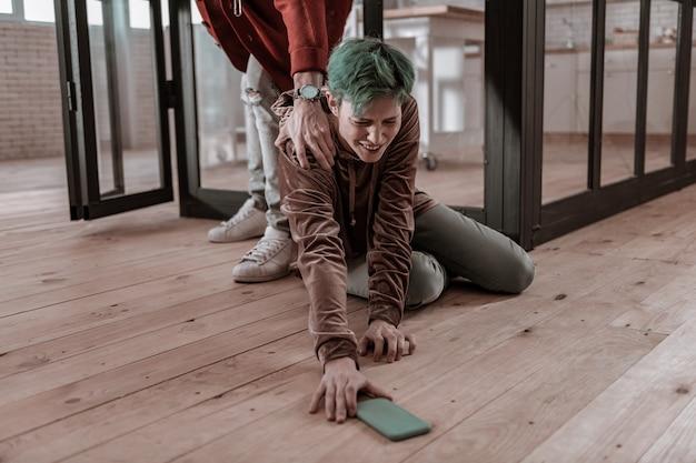 Blauwe smartphone. huilende vriendin die haar blauwe smartphone van de vloer haalt na nerveuze ruzie