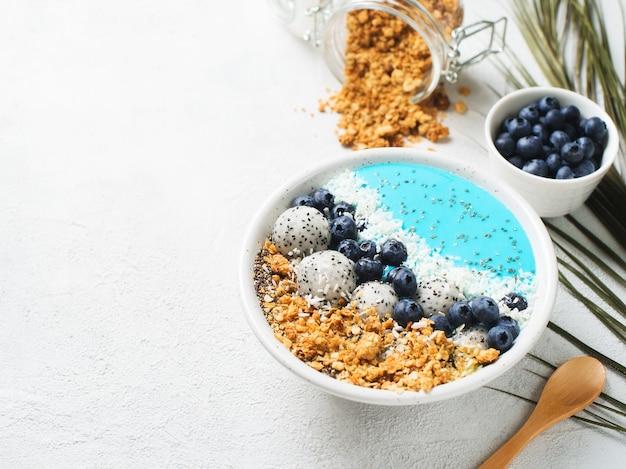 Blauwe smothie in kom met granola en bessen