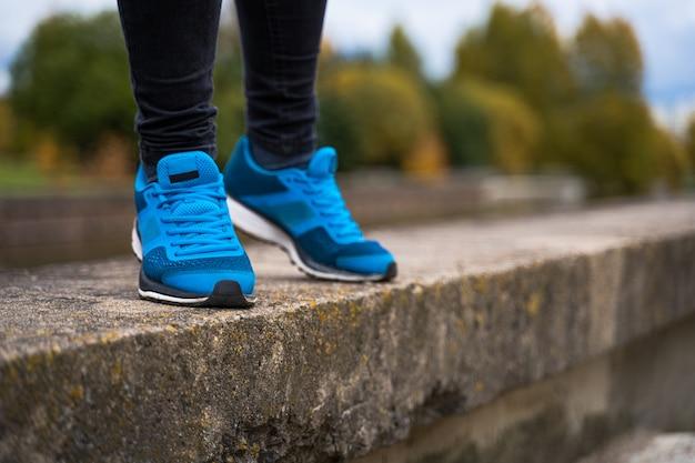 Blauwe sneakers op de benen van een vrouw.