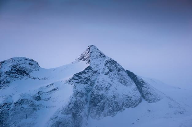Blauwe sneeuwpiek in sneeuwstorm in de ochtend