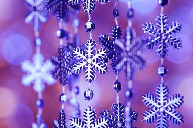 Blauwe sneeuwvlokken op de sjorring over de bokeh-achtergrond