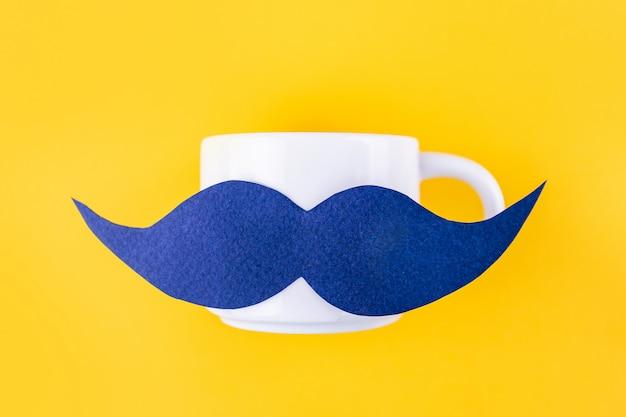 Blauwe snor op een koffiemok voor movemberconcept