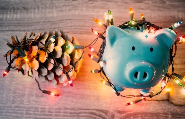 Blauwe spaarpot en dennenappel met feestverlichting, geniet van besparingen voor het vakantieconcept.