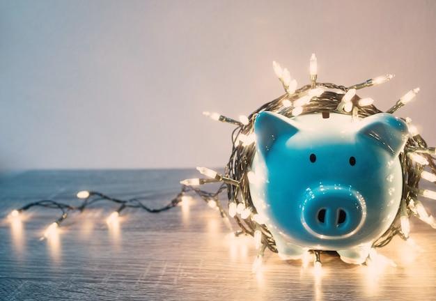 Blauwe spaarpot met feestverlichting, geniet van besparingen voor het vakantieconcept.