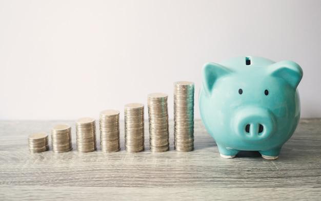 Blauwe spaarvarken met munten stapel groei grafiek, geld besparen voor toekomstig investeringsplan en pensioenfonds concept.