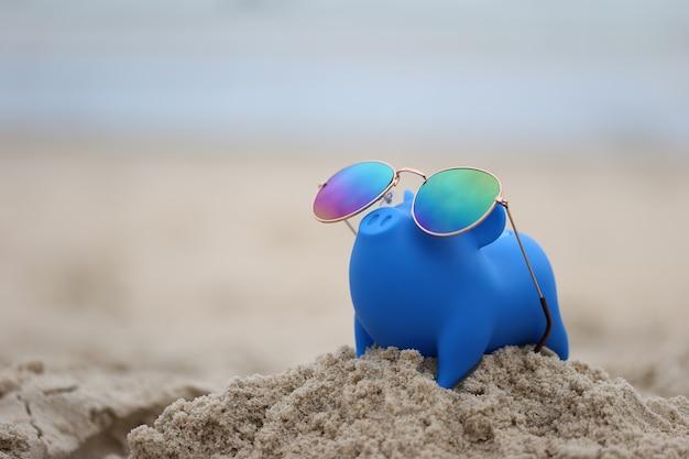 Blauwe spaarvarken met zonnebril op zee strand