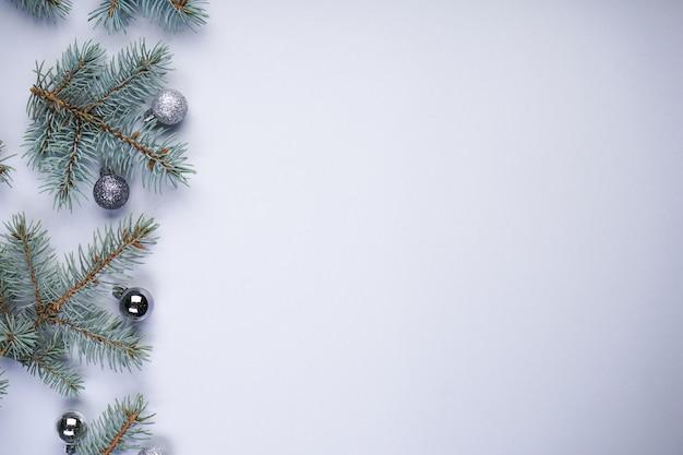 Blauwe sparren takken met kerstversiering op lichtgrijs met copyspace, plat leggen.