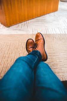 Blauwe spijkerbroek en bruine leren schoenen