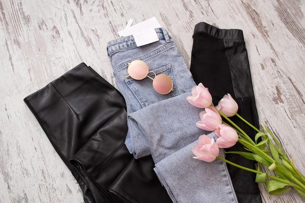 Blauwe spijkerbroek en zwarte lederen legging, bril, roze tulpen.