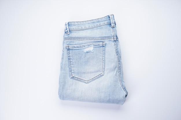 Blauwe spijkerbroek gevouwen op een wit, bovenaanzicht.