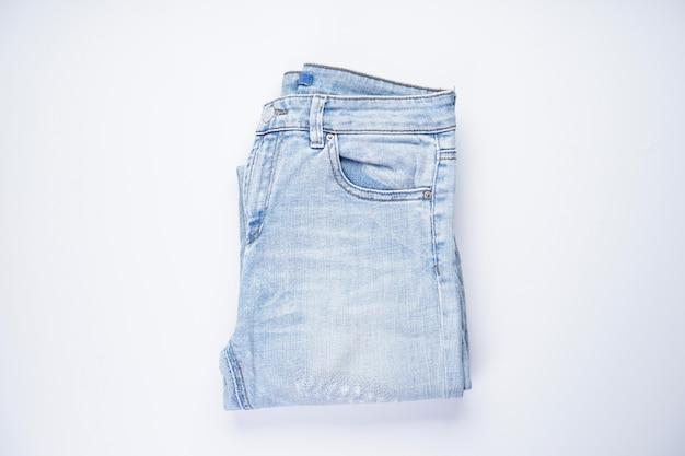 Blauwe spijkerbroek gevouwen op een witte plat leggen.