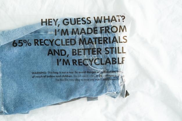 Blauwe spijkerbroek in plastic zak met label gerecyclede materialen en recyclebaar. nul afvalconcept.