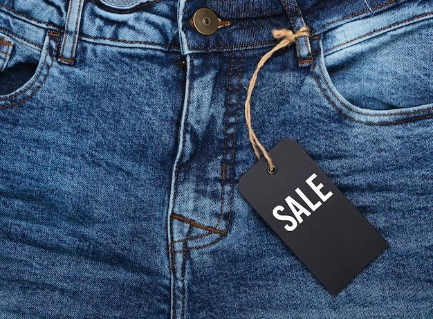 Blauwe spijkerbroek met een close-up van de verkoopmarkering. seizoensgebonden kortingen of zwarte vrijdag