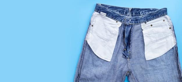 Blauwe spijkerbroek op blauwe muur.