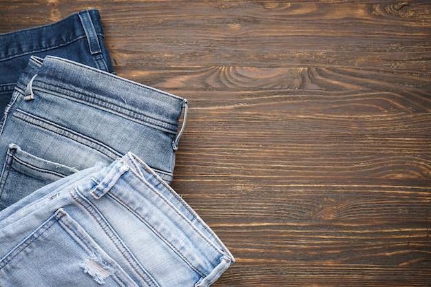 Blauwe spijkerbroek op bruine houten achtergrond, bovenaanzicht. ruimte voor tekst.