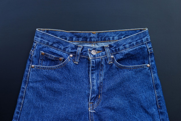 Blauwe spijkerbroek op donkere muur.