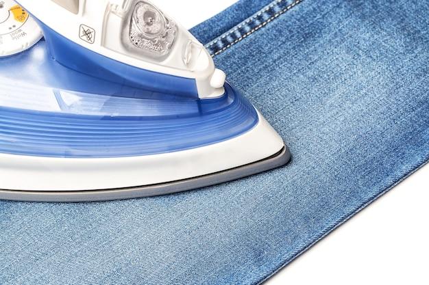 Blauwe spijkerbroek op een witte baclground strijken