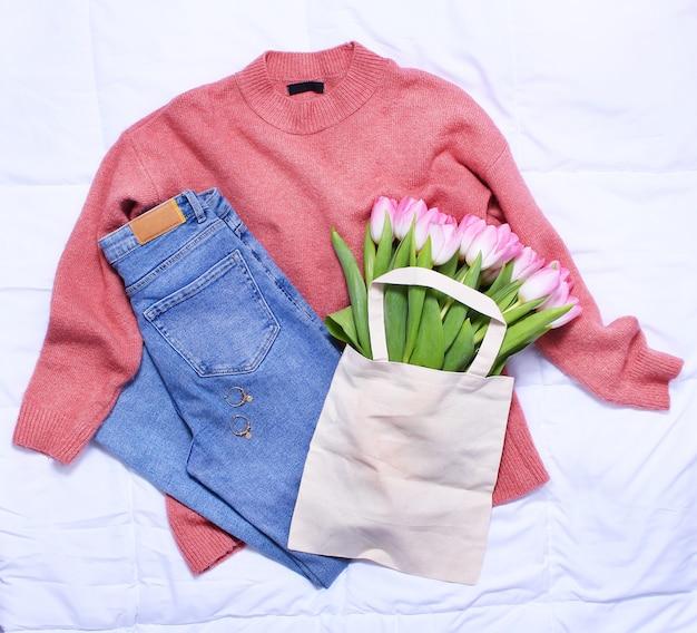 Blauwe spijkerbroek, roze trui en boeket roze tulpen