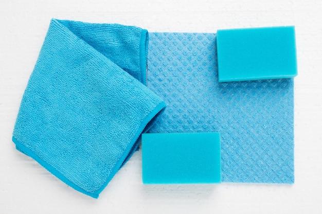 Blauwe sponzen, vodden, borstels op wit