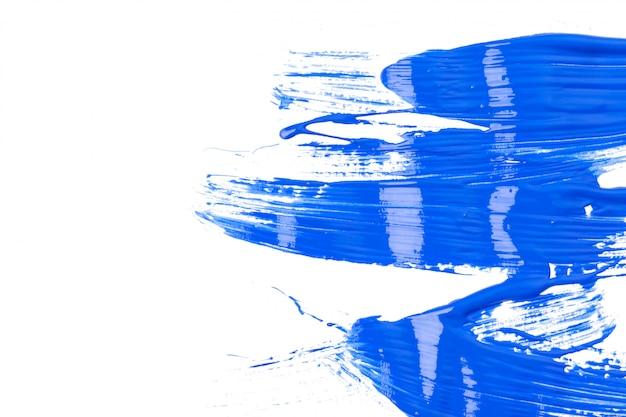 Blauwe sporen van verf geïsoleerd op een witte