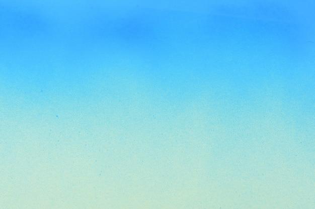 Blauwe spuitverf op een crèmekleurige papieren ondergrond