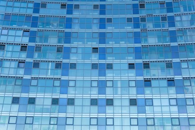 Blauwe stedelijke achtergrond - geglazuurde gevel van een modern gebouw met meerdere verdiepingen
