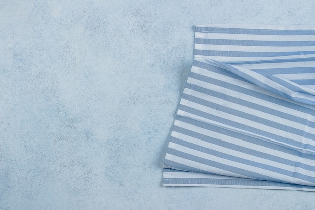 Blauwe stenen tafel met blauw gestreepte servet tafellaken.