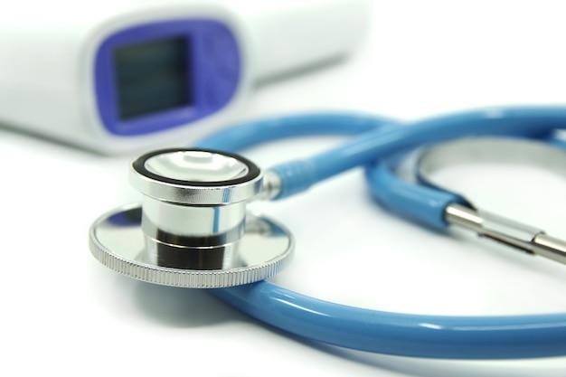 Blauwe stethoscoop en infrarood thermometer op wit oppervlak. medische hulpmiddelen voor behandeling. gezondheidszorg concept.